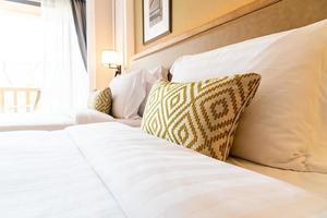 decoração de travesseiros confortáveis na cama do quarto do hotel foto