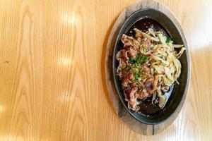 porco teriyaki em frigideira quente com repolho - comida japonesa foto