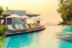 cadeiras de piscina ao redor de piscinas em hotel resort - conceito de feriados e férias foto