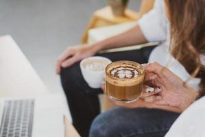 mulher asiática e homem sentado no café e desfrutar de beber expresso. conceito de cafeteria foto