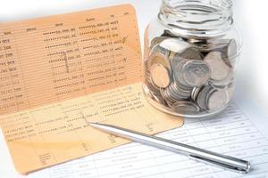 caneta no banco do livro de conta com moedas na banca de frasco de vidro, investimento, economia, conceito de negócio. foto