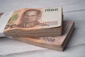 pilha de notas de baht tailandês em fundo de madeira, conceito de investimento financeiro de economia de negócios. foto