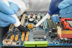 O técnico usa uma escova e uma bola de soprador de ar para limpar a poeira no computador da placa de circuito. atualização de reparação e tecnologia de manutenção. foto