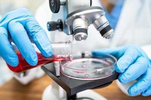 cientista asiático bioquímico ou microbiologista trabalhando em pesquisa com um microscópio no laboratório. para proteger surto de coronavírus covid19, bactérias e germes. foto