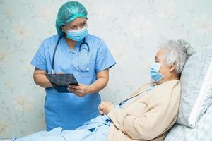 médico asiático usando protetor facial e terno de ppe e segurando o tablet novo normal para verificar o paciente protege o surto de coronavírus covid-19 de infecção de segurança na enfermaria de quarentena do hospital de enfermagem. foto