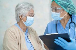 médico asiático usando protetor facial e terno novo normal para verificar o paciente protege a segurança infecção covid-19 surto de coronavírus na enfermaria de quarentena do hospital. foto