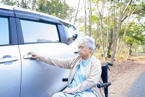 paciente asiático sênior ou idosa senhora sentada na cadeira de rodas preparar chegar ao carro dela, conceito médico forte saudável. foto