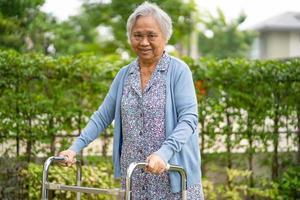 Mulher idosa idosa ou sênior asiática usa andador com saúde forte enquanto caminha no parque em um feriado feliz foto