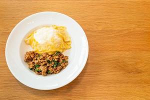 Carne de porco frita e manjericão com omelete cremosa no arroz - comida asiática foto