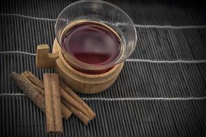 uma xícara de vinho quente em um fundo preto com paus de canela foto