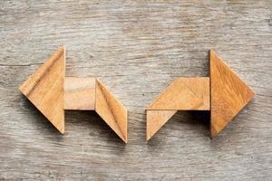 quebra-cabeça tangram em forma de seta bidirecional em fundo de madeira foto