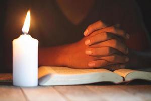 conceitos religiosos, o jovem orou sobre a bíblia na sala e acendeu as velas para iluminar. foto