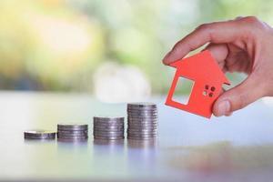 mãos segurando um modelo de casa. plano de hipotecas do setor imobiliário e estratégia de economia de impostos residenciais, hipotecas, investimentos, imóveis e conceito de propriedade foto