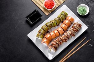 Saborosos rolos de sushi frescos dispostos na forma de um dragão com gengibre e wasabi foto