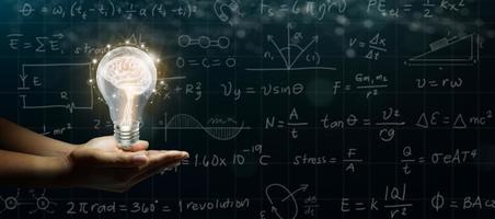 mão de empresário segurando o cérebro humano brilhando dentro de uma lâmpada em fundo abstrato de esboços escuros foto