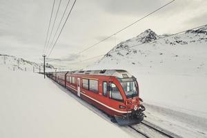 trem vermelho expresso de bernina perto do passo de bernina nos Alpes suíços foto