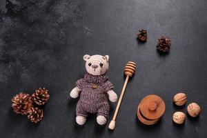 urso de brinquedo amarrado com fios de lã em um fundo escuro foto