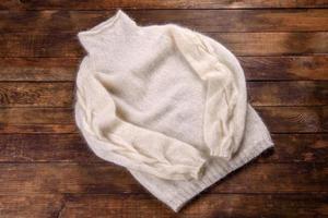 Suor tricotado de fios de lã em fundo escuro foto