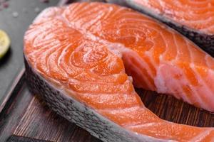 bife de salmão cru fresco com especiarias e ervas preparadas para assar na grelha foto