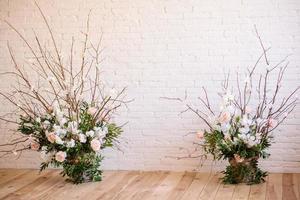 decorações de ramos com lindas flores rosa e brancas na cesta contra o fundo de uma parede de tijolos brancos foto