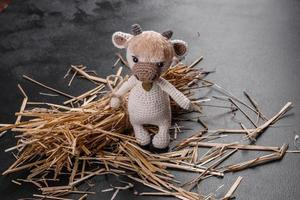 touro de brinquedo de malha de fios claros em um fundo escuro foto