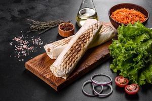 delicioso shawarma fresco com carne e vegetais em uma mesa de concreto escura foto