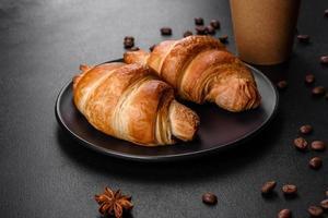 Crocante fresco e delicioso croissant francês com uma xícara de café perfumado foto