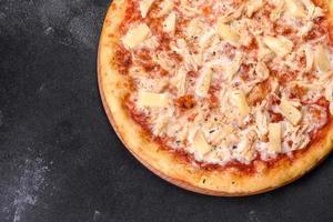 saborosa pizza fresca de forno com tomate, queijo e abacaxi em um fundo escuro de concreto foto