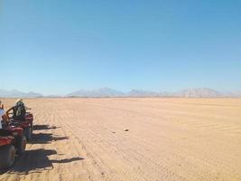 um grupo de pessoas em quadriciclos no deserto do Egito foto