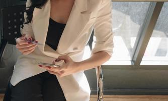 mulher segurando um cartão de crédito e usando smartphone no escritório foto
