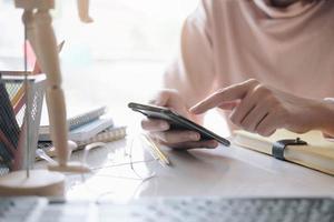 mulher segurando um smartphone e usando um laptop em casa foto