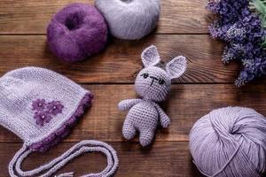 lebre de brinquedo amarrada com fios de lã em um fundo escuro foto