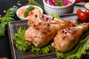 saborosas pernas de frango grelhado com especiarias e ervas em uma placa de madeira sobre um fundo escuro de concreto foto