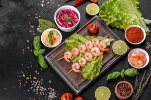 saboroso camarão preparado na hora com especiarias e ervas em uma placa de madeira sobre um fundo escuro de concreto foto