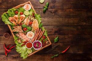 composição de salsichas, frango, porco e camarão preparado na grelha, bem como vegetais preparados na grelha com especiarias e ervas foto