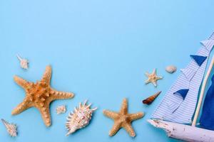 óculos e chapéu com conchas e estrelas do mar em um fundo colorido foto