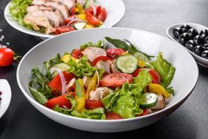 deliciosa salada fresca com frango, tomate, pepino, cebola e verduras com azeite de oliva foto