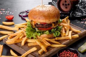 delicioso hambúrguer fresco com costeleta de carne, tomate e alface com batata frita foto