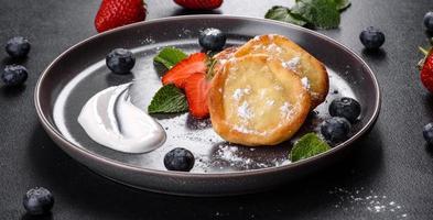 saborosas panquecas assadas com frutas e hortelã com açúcar de confeiteiro e cobertura em um prato cinza foto