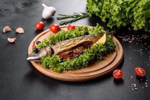 cavala assada com legumes em uma placa de madeira com limão foto