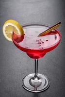 O coquetel alcoólico é cosmopolita com gelo, frutas vermelhas e tubos de coquetel foto