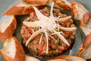 tártaro de salmão cru. Salada de salmão fresco, abacate e rúcula em um anel culinário foto