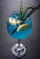 Coquetel alcoólico Curaçao azul com gelo, limão e tubos de coquetel foto