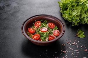 pedaços de frango, tomate e folhas de alface em um fundo escuro de concreto foto