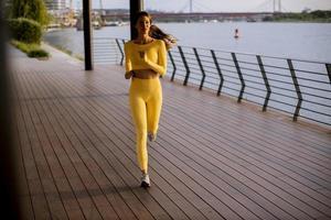 jovem fazendo exercícios de corrida à beira do rio foto