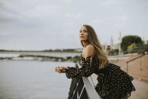 jovem morena de cabelos longos em pé à beira do rio foto