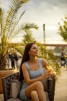 jovem bebendo suco de laranja no café da rua foto