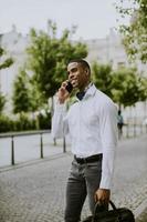 jovem empresário afro-americano usando um telefone celular foto