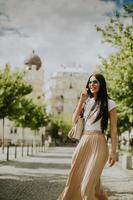jovem usando um telefone celular enquanto caminha na rua foto
