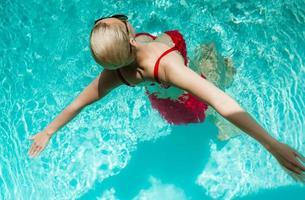 jovem linda garota sexy nadando na piscina privada e relaxando ao sol foto